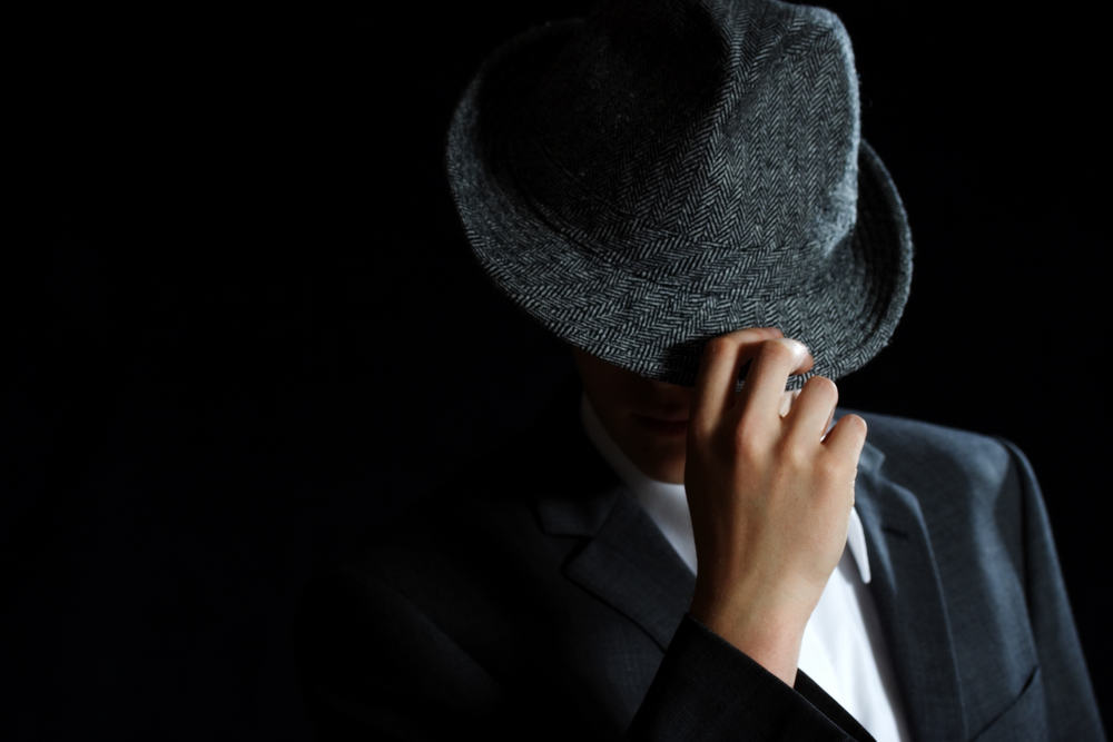 This is a man wearing a dark gray trilby hat.
