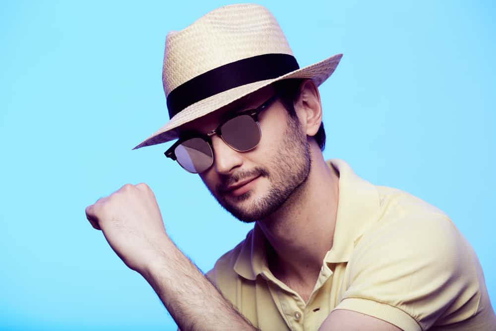 A man wearing yellow polo shirt and a fedora.