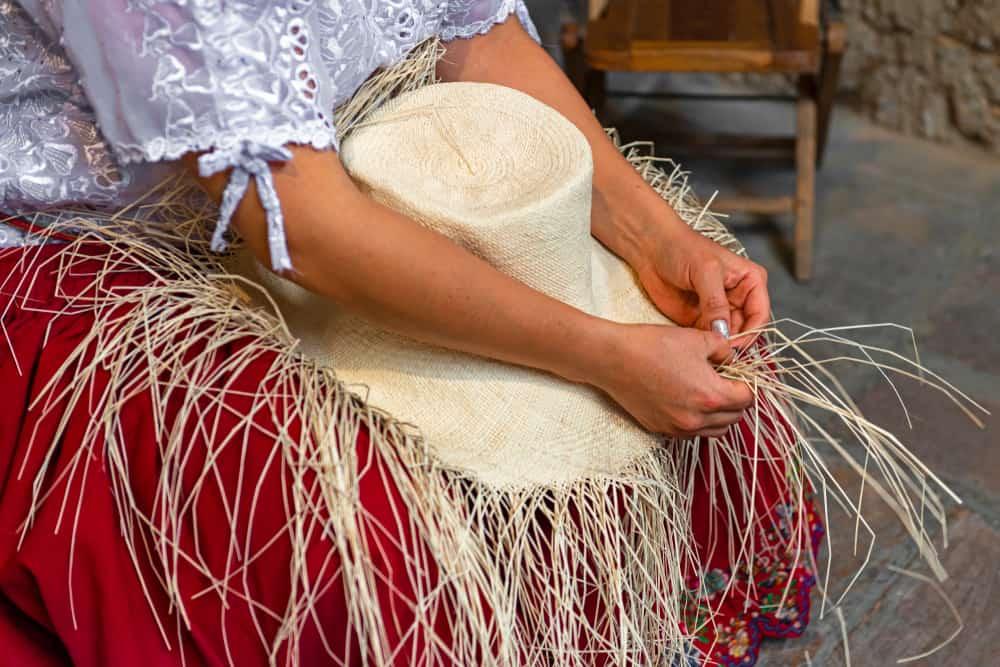 A close look at a woman weaving a Panama hat.