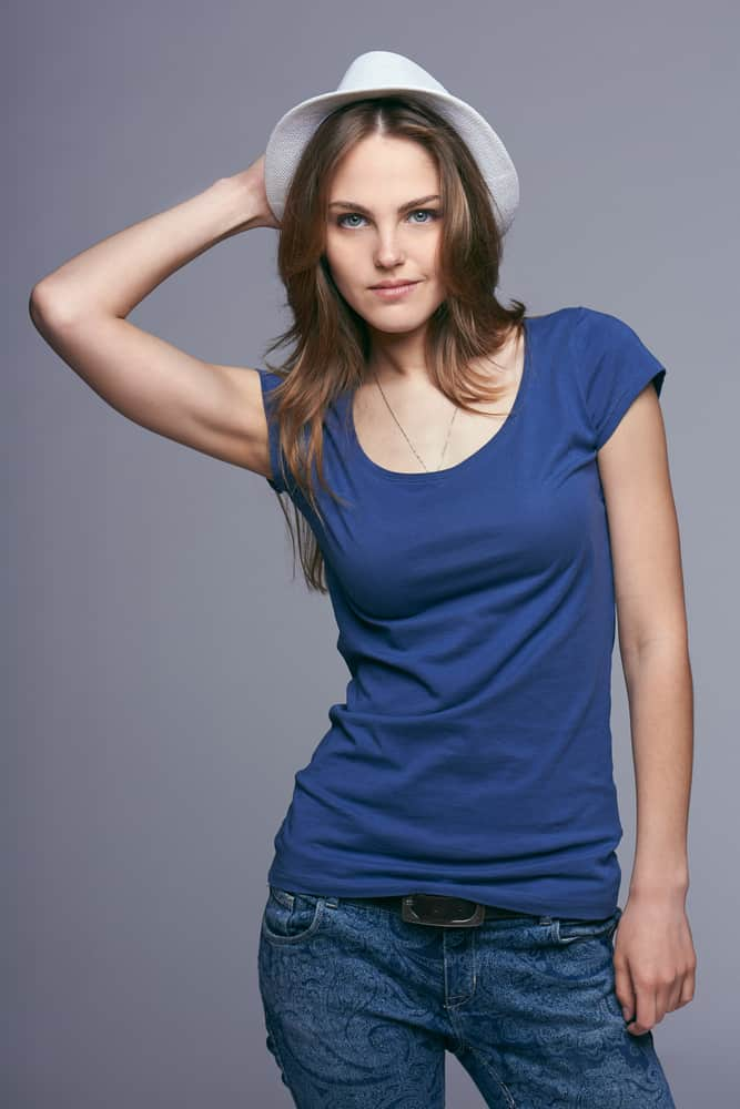 A woman wearing jeans, tank top and fedora.