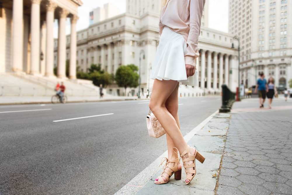 This is a close look at a woman wearing a cream blouse, a white skirt and a pair of strappy sandals.