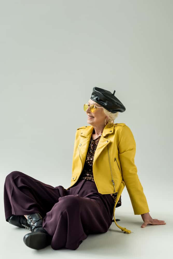 This is a woman wearing a black leather beret with her yellow leather jacket.