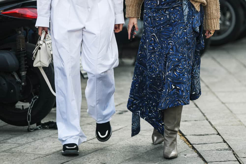 A close look at a woman wearing a blue patterned maxi skirt with her gray leather boots.