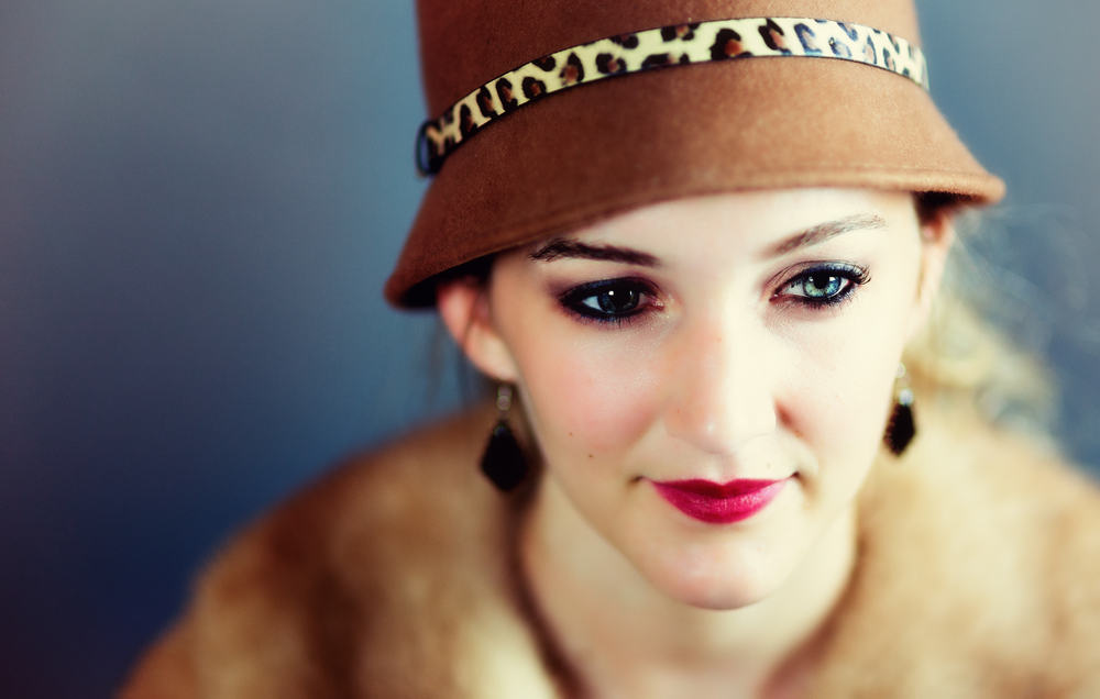 This is a close look at a woman wearing a vintage brown cloche hat.
