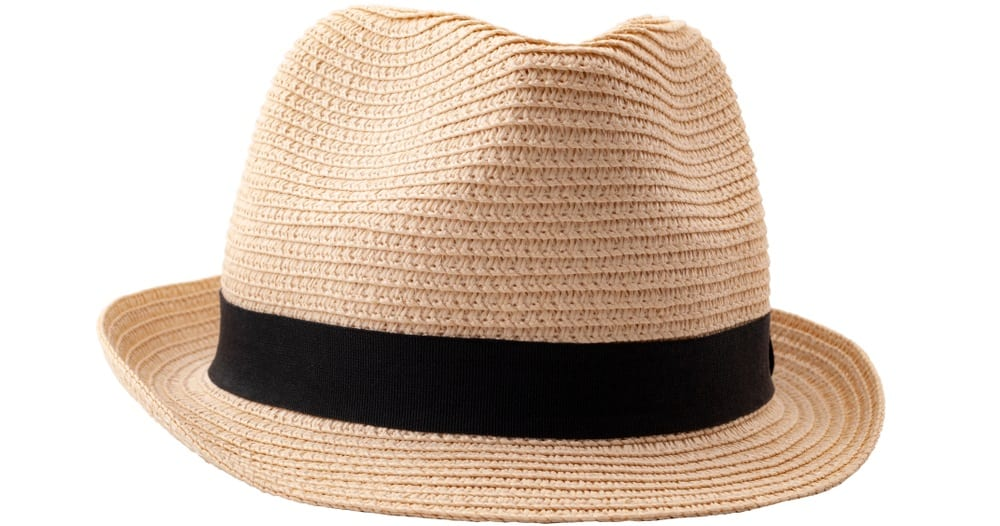 A close look at a woven straw fedora hat that has a black band.
