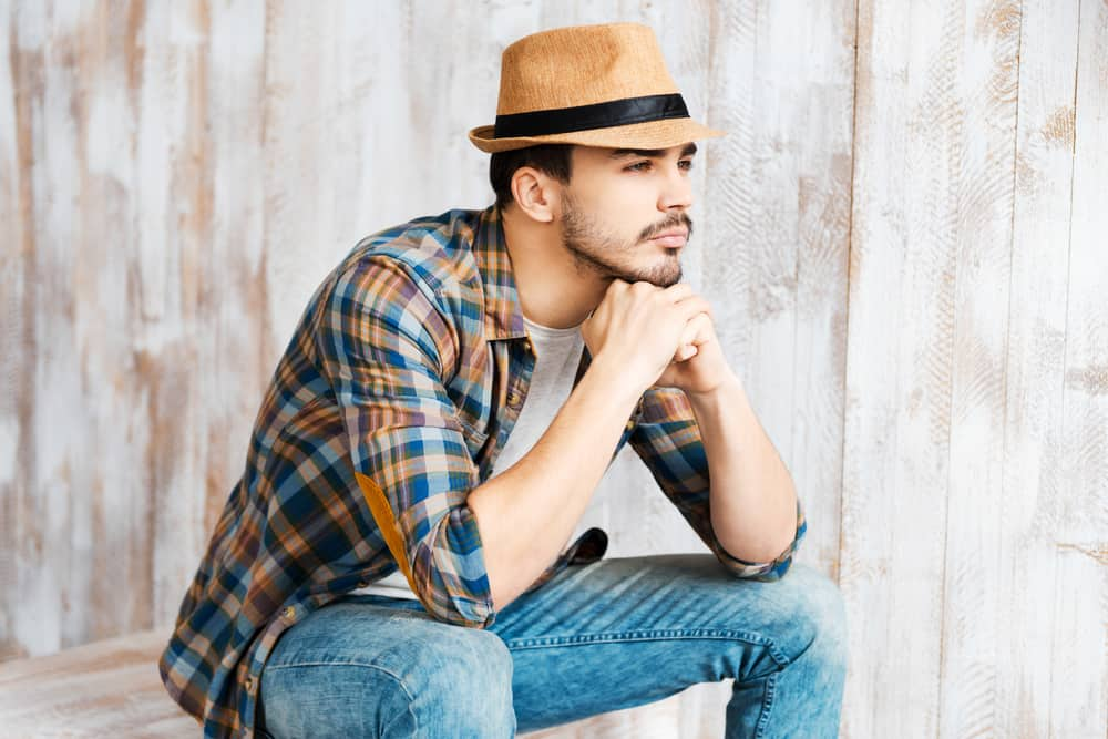 This is a man wearing a plaid shirt and blue jeans with his brown fedora.