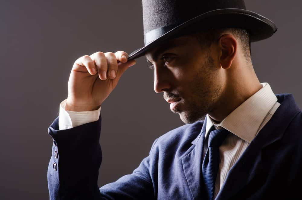 A man wearing a dark suit and a fedora.