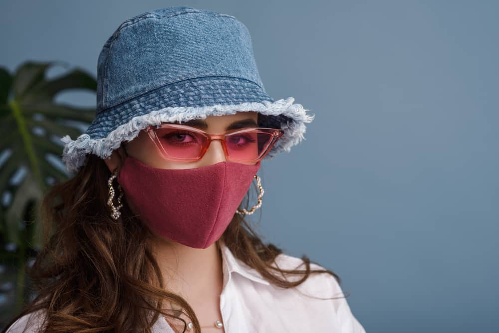 A woman wearing a denim bucket hat and a pink face mask.