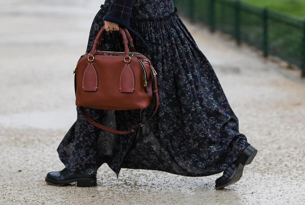This is a woman wearing a floral maxi skirt with her black leather heel boots.