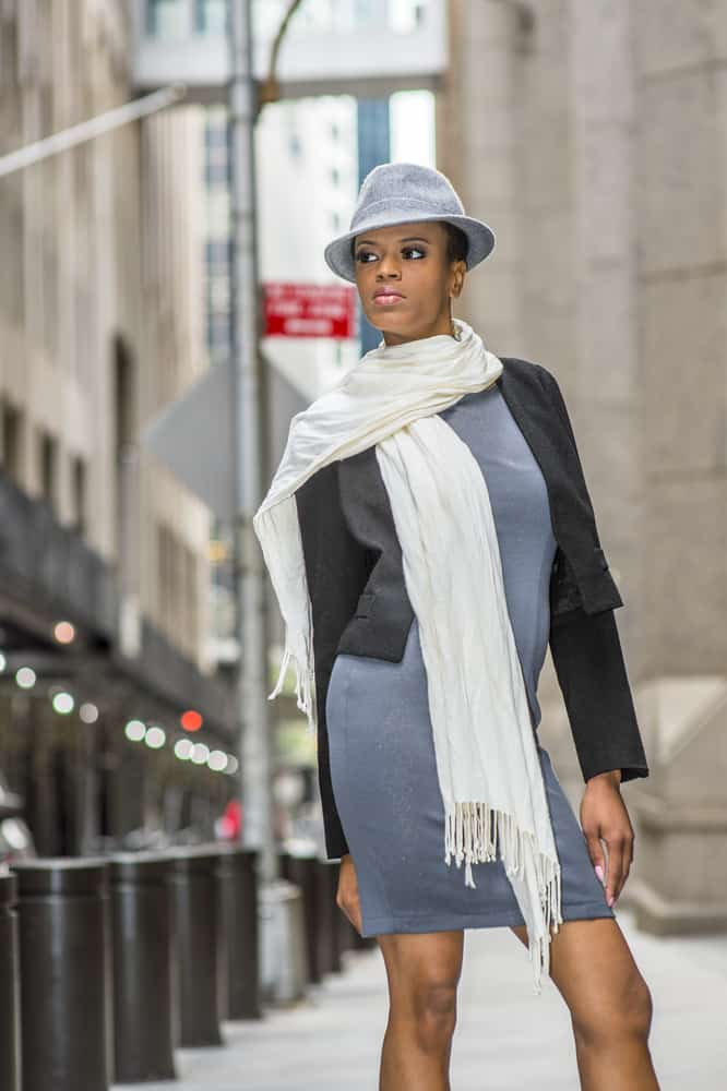 This is a woman wearing a gray dress, matching gray fedora and a white scarf.