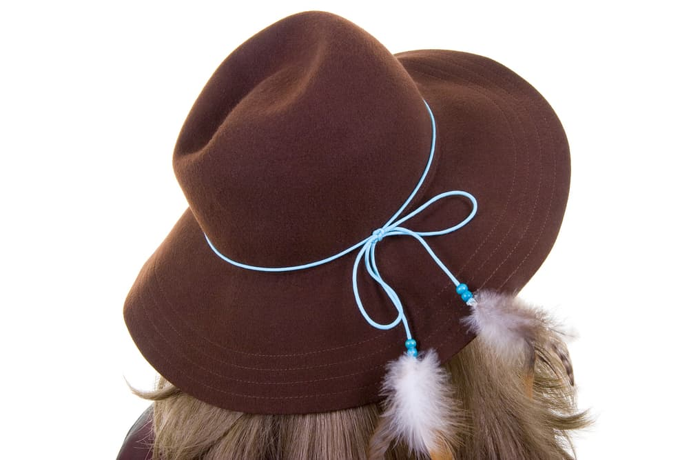 A woman wearing a brown fedora embellished with feathers.