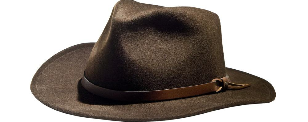This is a close look at a felt fedora hat with a wider brim and a leather band.