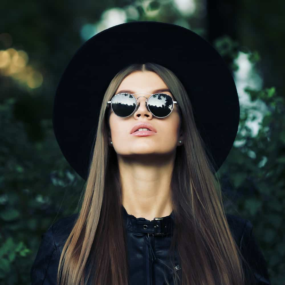 This is a long-haired woman wearing a wide-brimmed hat and black leather jacket.
