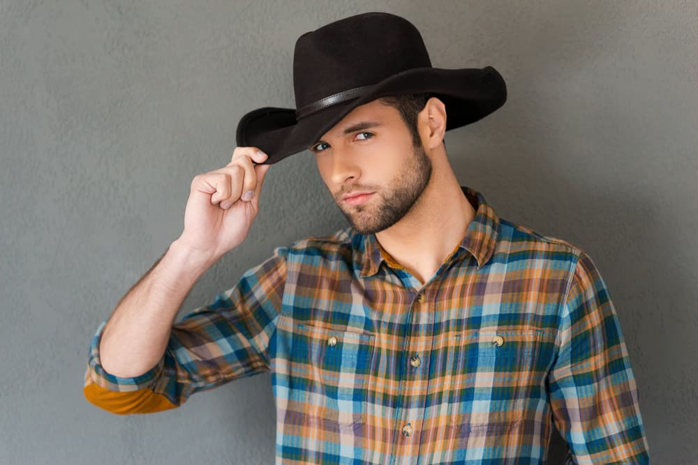 This is a man wearing a plaid shirt with his dark cowboy hat.