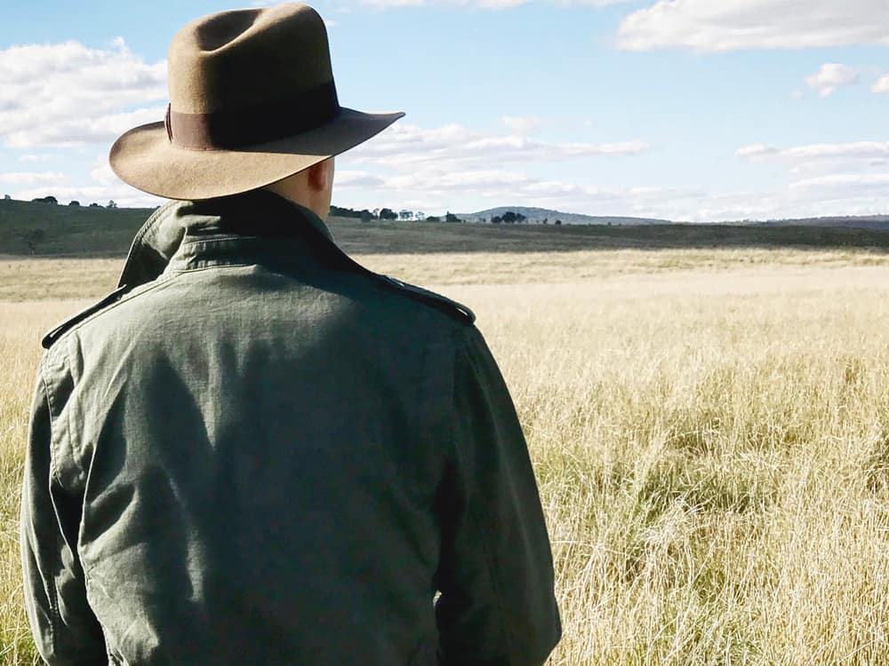 This is a close look at a man wearing a safari hat at a grass field.