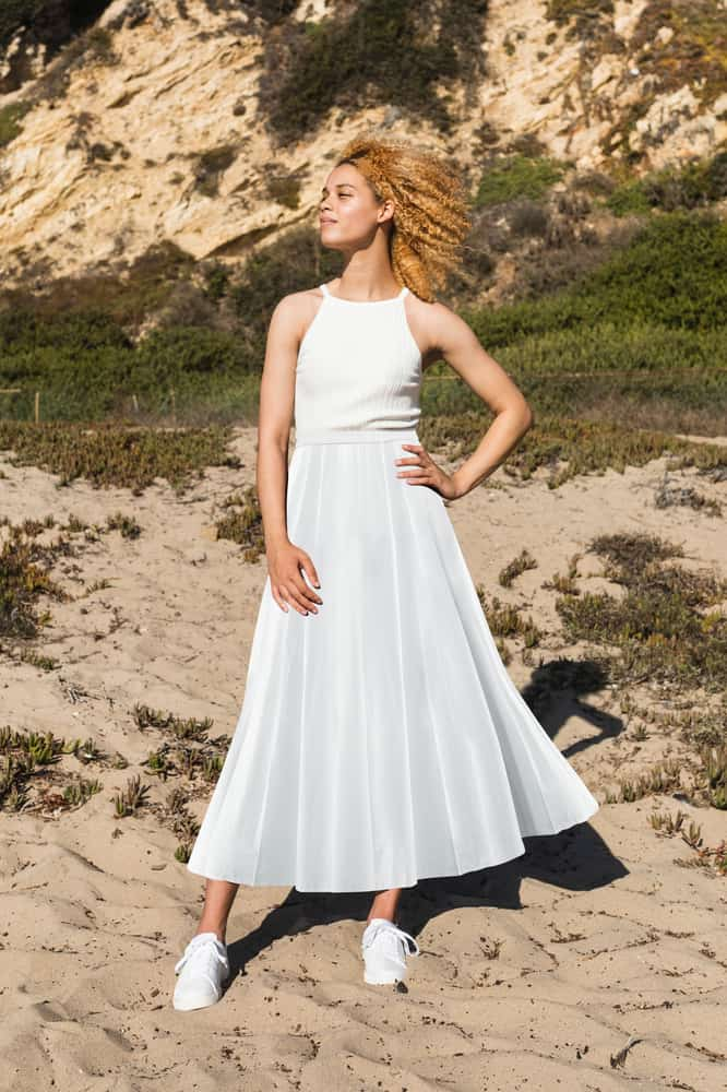 A woman wearing a white top, a white maxi skirt and a pair of white sneakers.