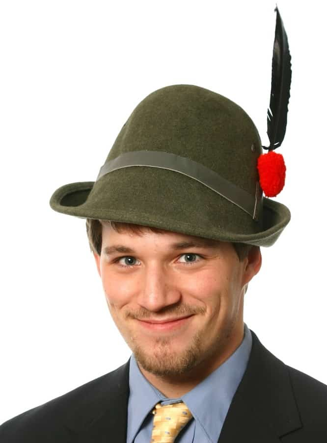 A man wearing a green alpini hat that has a tall feather on the side.