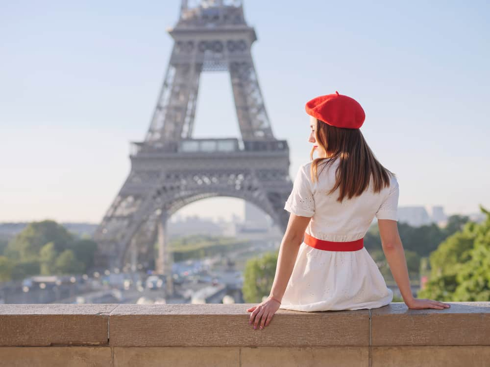 A woman wearing a red French beret with her dress.