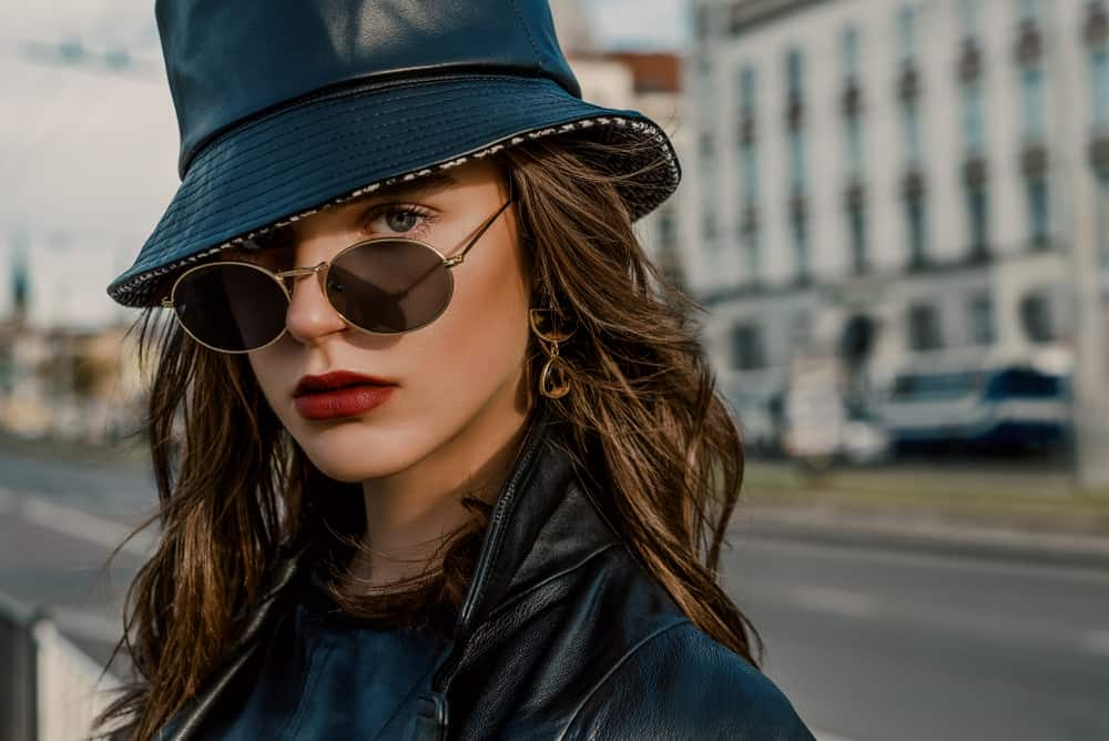 A woman wearing a black leather bucket hat to match her black leather jacket.