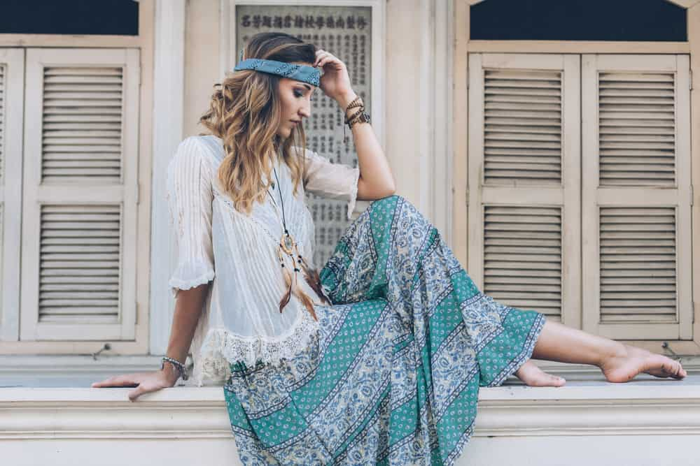This is a woman wearing a white sheer blouse with her patterned maxi skirt that matches her headband.