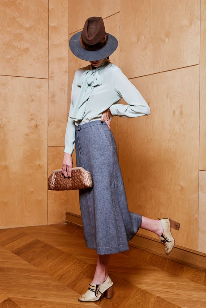 A woman wearing a long gray skirt, blouse and a fedora.
