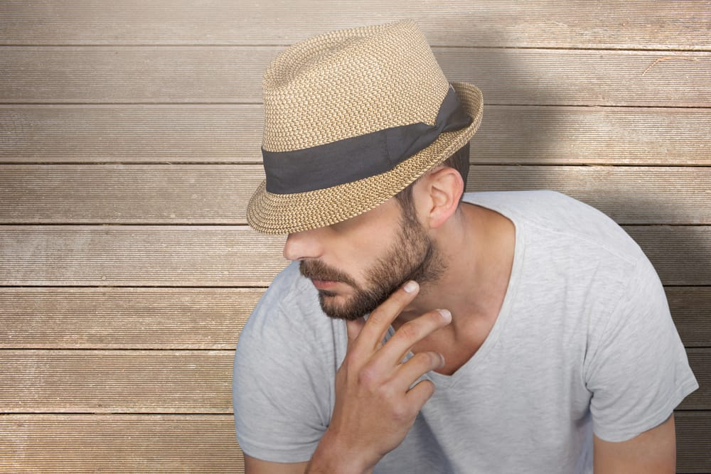 This is a close look at a bearded man wearing a gray shirt and a trilby hat.
