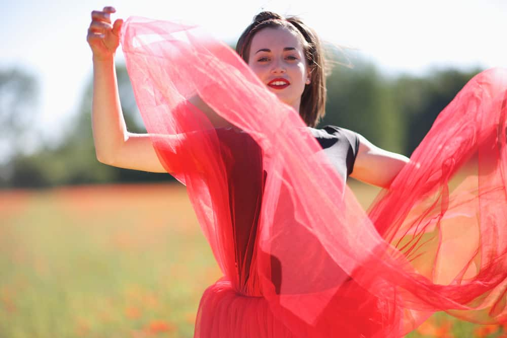 This is a woman fluttering her red tulle layered skirt.
