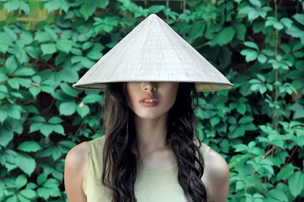 This is a woman wearing a straw conical hat.