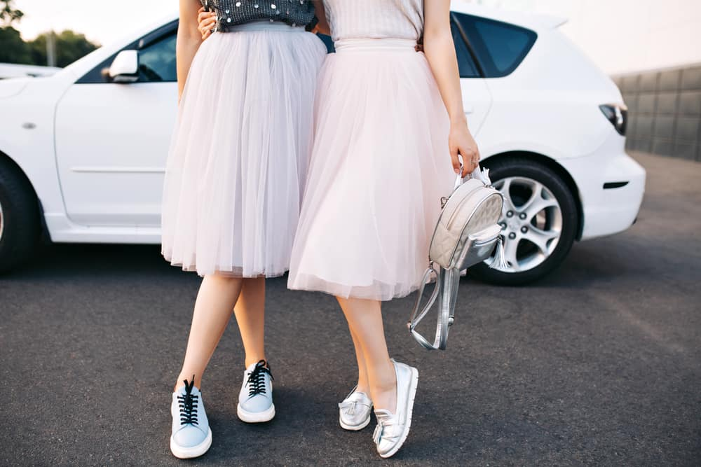 This is a close look at a couple of women wearing tulle skirts and sneakers.