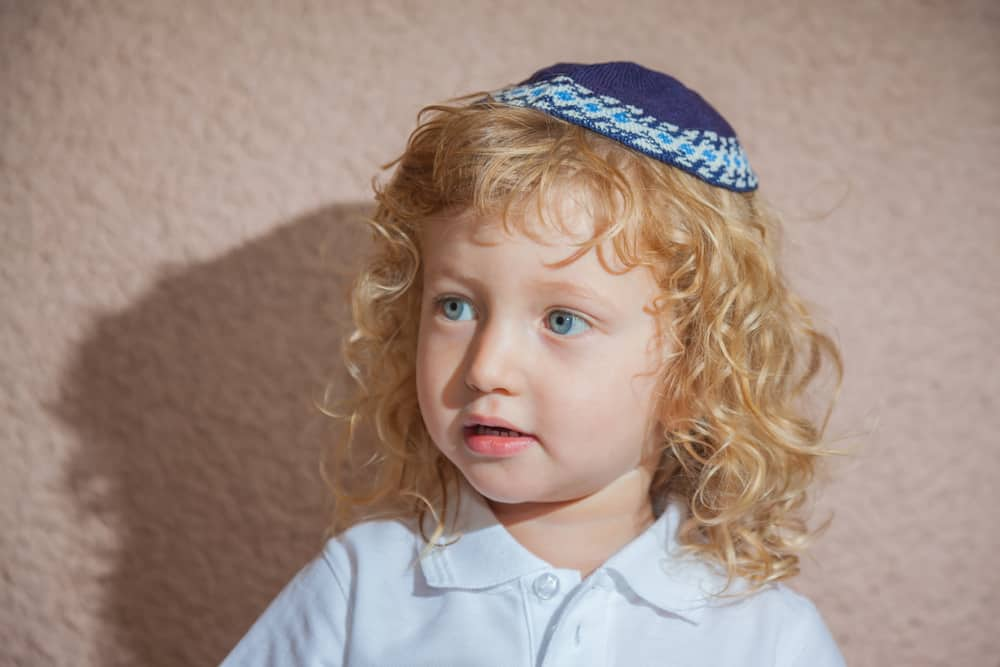 This is a close look at a young Jewish child wearing a blue knit yarmulke hat.