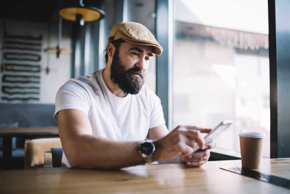 This is a bearded man wearing a white shirt and an ivy cap at a coffee shop.