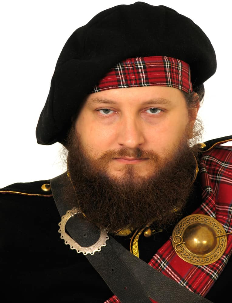 This is a man wearing a vintage Scottish warrior costume topped with a bonnet.