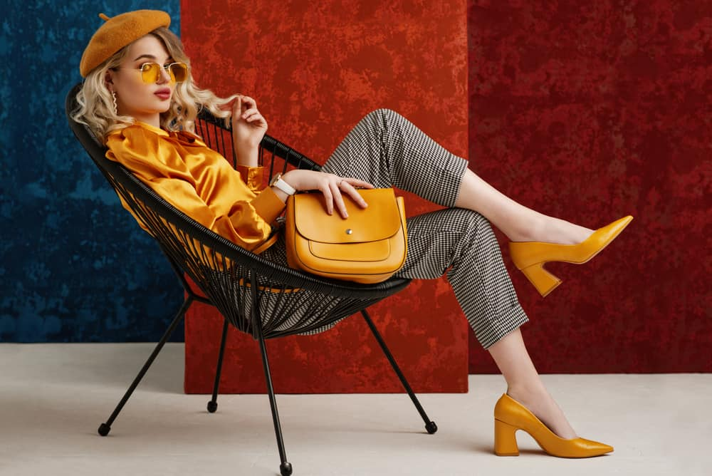 This is a fashionable woman wearing matching mustard blouse, shoes and beret.