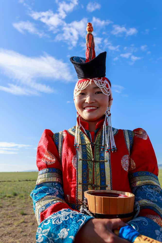 A woman wearing a colorful traditional Mongolian dress with a boqta.