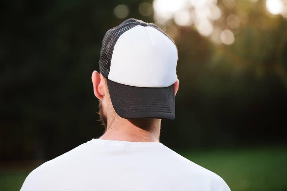 This is a close look at a man wearing a baseball cap backwards.
