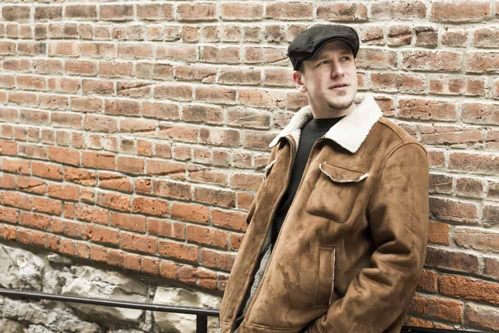 This is a man wearing a brown aviator jacket and newsboy cap.