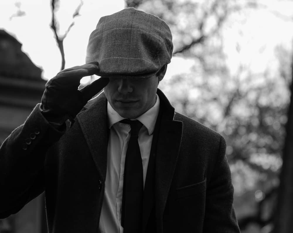 This is a close look at a man wearing a suit, leather gloves and an ivy cap.