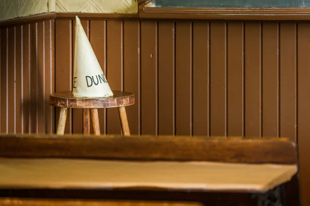 The conical dunce hat on a wooden stool in the classroom.