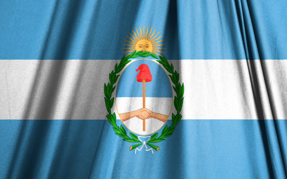 This is the Argentina flag with coat of arms in the middle that has a hat.