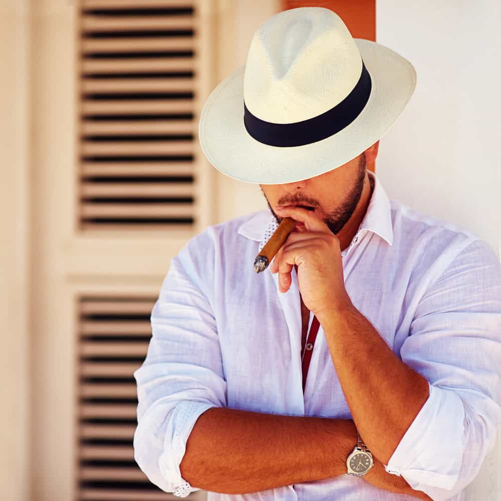 This is a man wearing a panama hat while smoking his cigar.