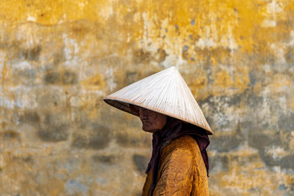 This is an old woman wearing a large straw conical hat.