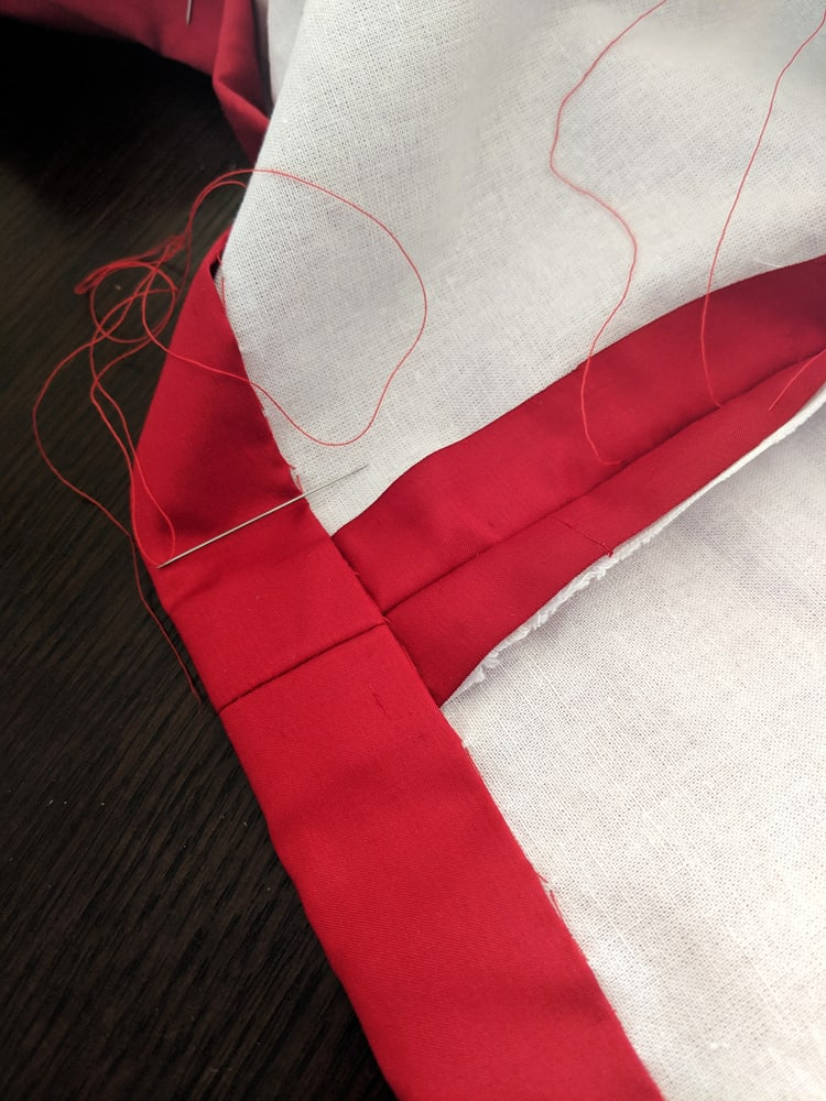 This is a close look at a red skirt being sewed at the hem line.