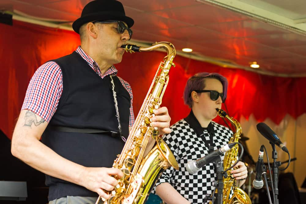 This is a close look at a performing saxophone player wearing a pork pie hat.