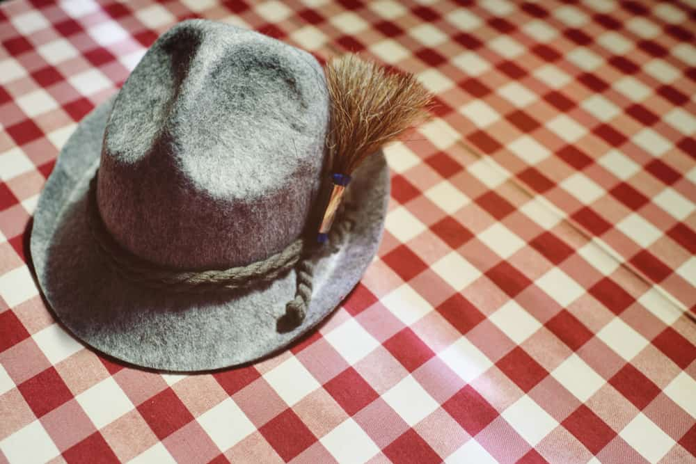 This is a close look at a gray traditional Bavarian hat on a picnic cloth.