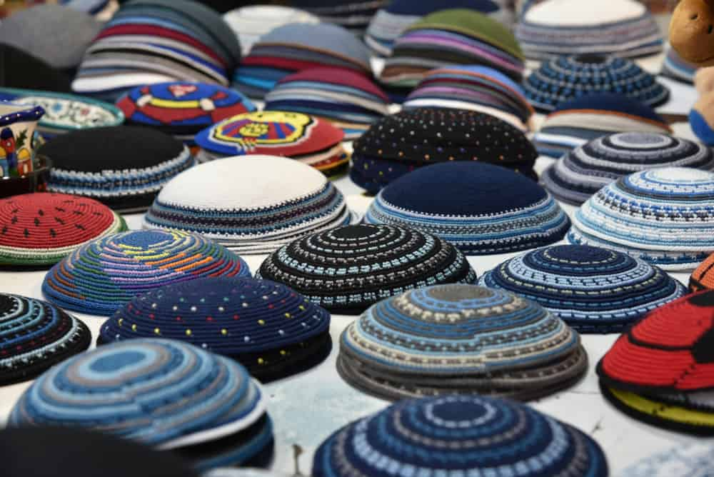 This is a close look at various colorful yarmulke hats on display.