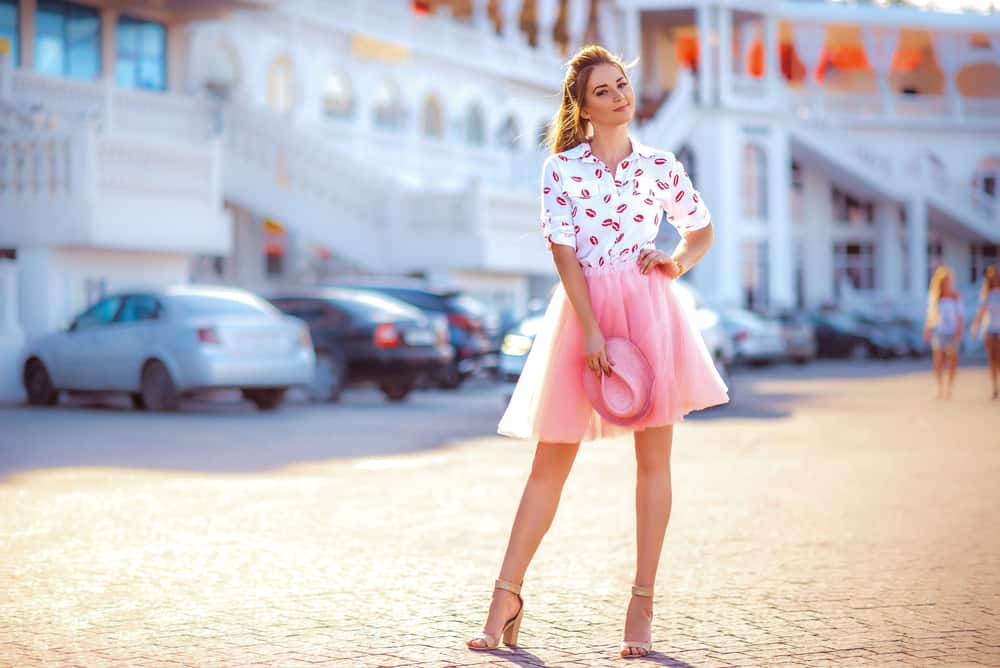 This is a woman wearing a pair of strappy heels, above-the-knee tulle skirt and a buttoned blouse.