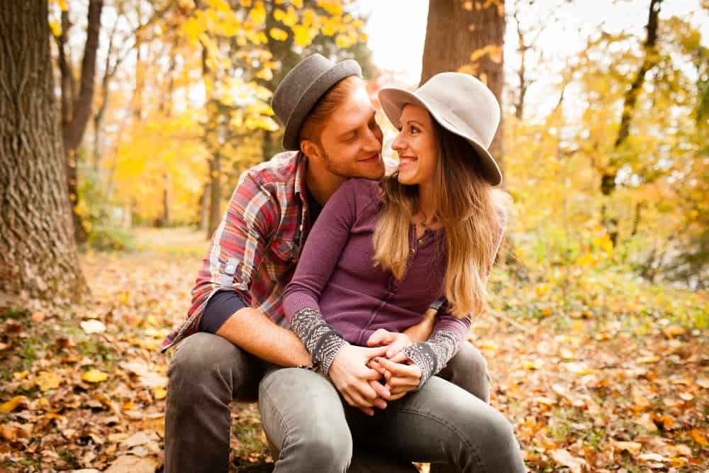 This is a couple in a forest during fall with the man wearing a pork pie hat.