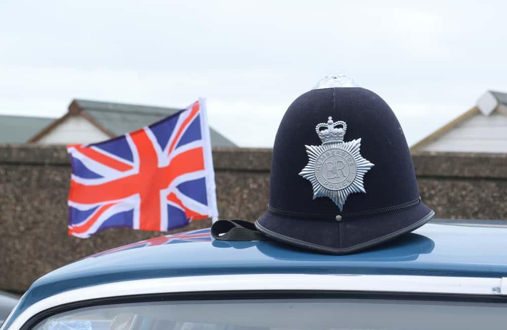 The dark Humberside police custodian hat on a car roof.