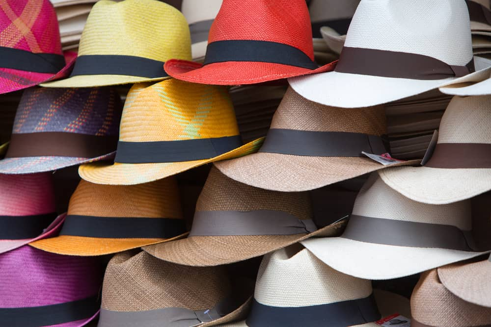 Stacks of panama hats on display in various colors.