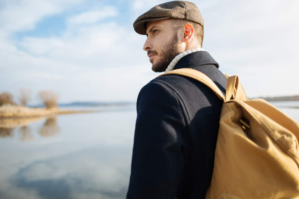 This is a traveling man wearing a jacket and an ivy cap while carrying his backpack.